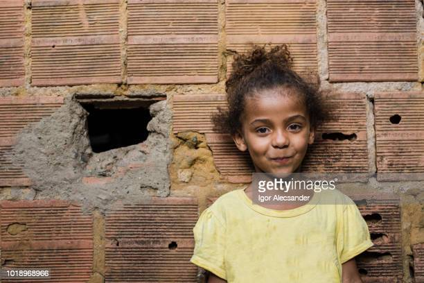 menina brasileira em uma parede de tijolo - com fome - fotografias e filmes do acervo