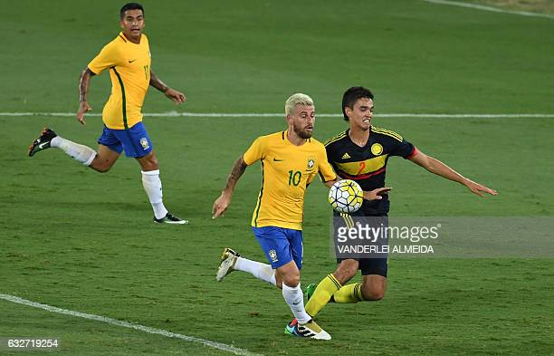 Brazilian Lucas Lima contests the ball with Farid Diaz of Colombia during a friendly football match in benefit of Chapecoense football team at the...