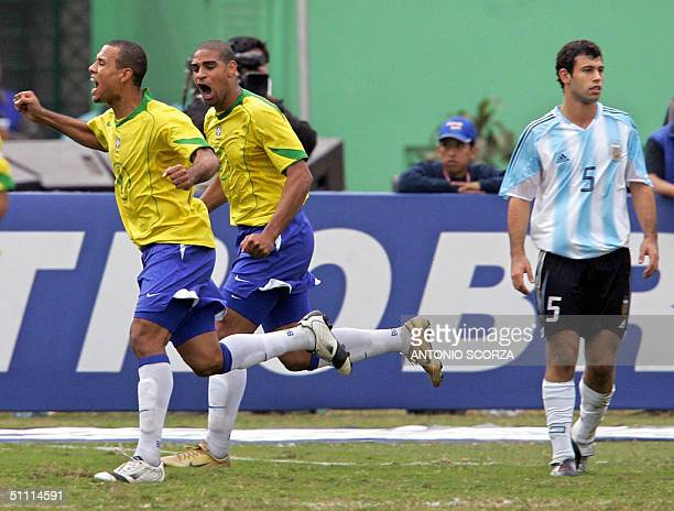 Brazilian Luis Fabiano and Adriano celebrate Brazil's first goal while Argentine midfilder Javier Mascherano shows his disappointment 25 July 2004...