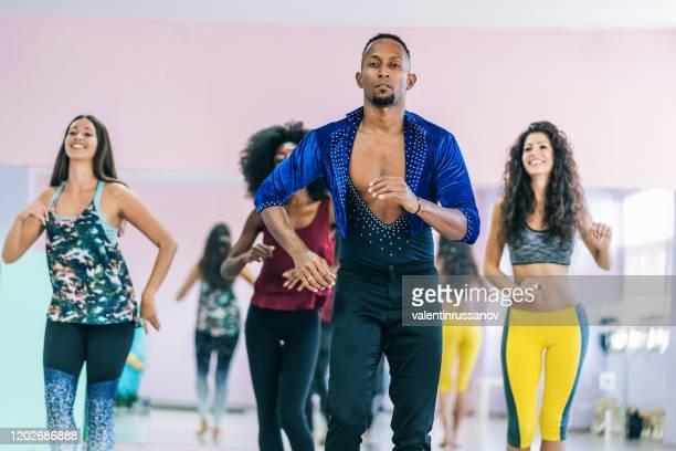 enseignant et étudiants masculins brésiliens pratiquant dans le studio - danse latine photos et images de collection
