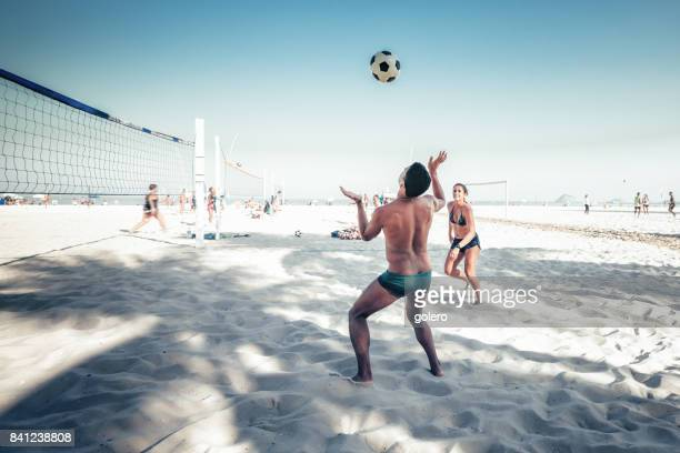 brazilian man and woman playing footvolley at beach in rio de janeiro - beach volleyball stock pictures, royalty-free photos & images