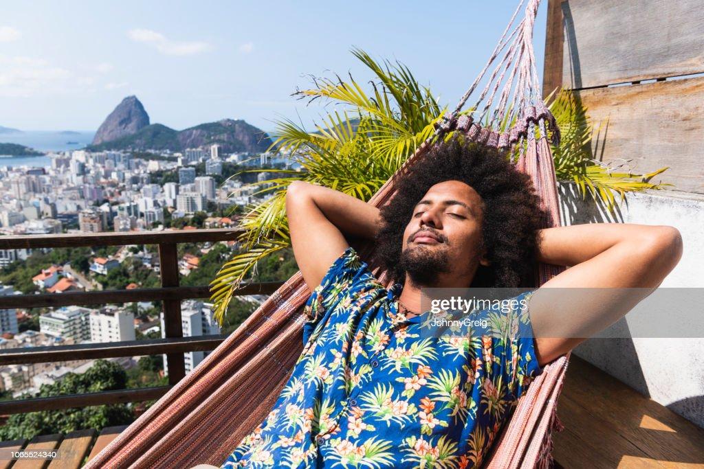 Brazilian man asleep on hammock, Sugar Loaf Mountain in distance : Stock Photo