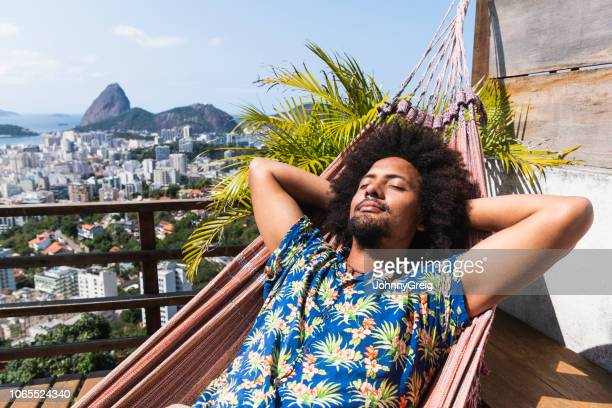 brazilian man asleep on hammock, sugar loaf mountain in distance - serene people stock pictures, royalty-free photos & images