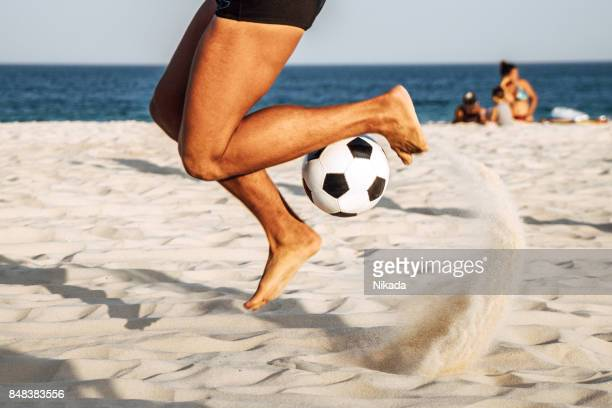 brazilian man bouncing soccer ball on beach, rio de janeiro, brazil - copacabana beach stock pictures, royalty-free photos & images