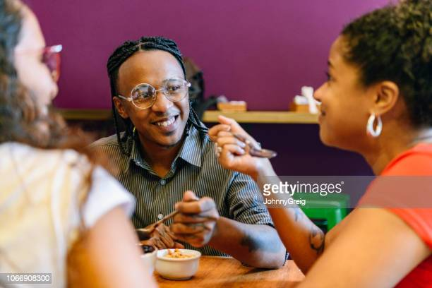 brazilian man enjoying açai with two female friends - acai stock pictures, royalty-free photos & images