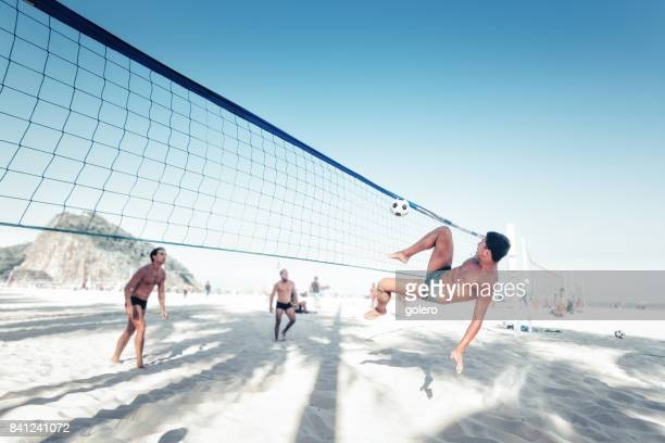 brazilian man kicking soccerball over volleyball net in rio - copacabana beach stock pictures, royalty-free photos & images