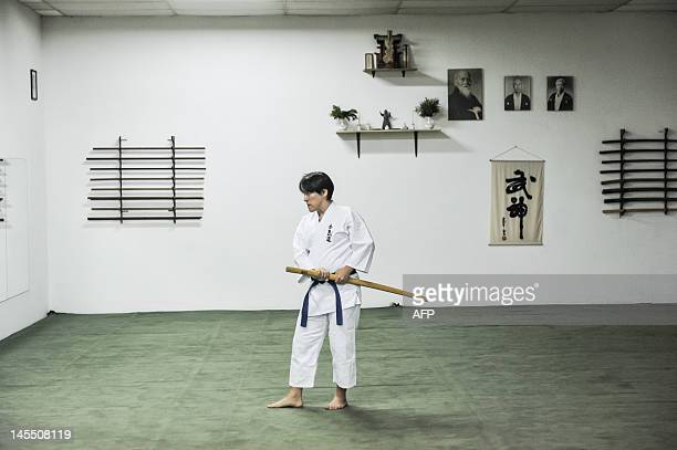 A Brazilian man practices Japanese martial art Aikido with a wooden sword in Sao Paulo Brazil on May 31 2012 AFP PHOTO/Yasuyoshi Chiba