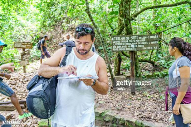brazilian man signing disclaimer on dangerous trail - disclaimer stock pictures, royalty-free photos & images