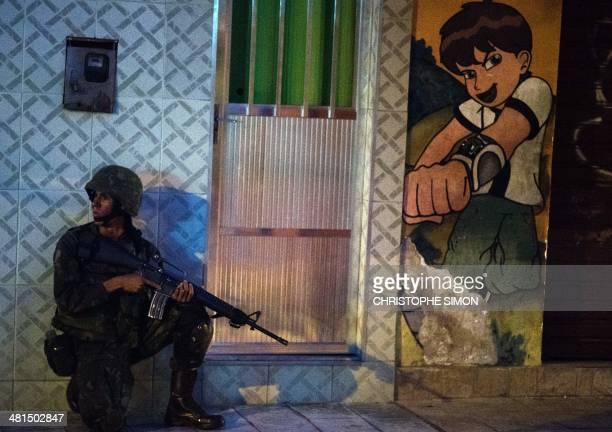 Brazilian marines patrol along a street of the Nueva Holanda favela part of the Favela da Mare shantytown complex in Rio de Janeiro Brazil on March...