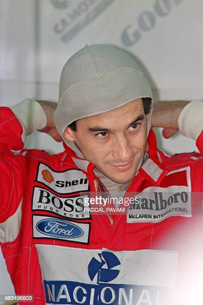 Brazilian McLaren driver Ayrton Senna adjusts his protective headgear before the second qualifying practice session 25 September 1993 at the Estoril...