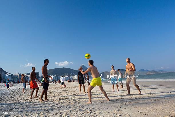 Brazilian men playing football on Copacabana beach Rio de Janeiro