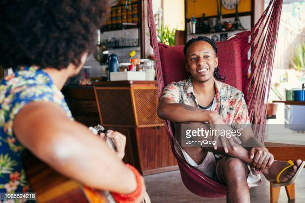 brazilian men relaxing, one playing guitar - hostel stock pictures, royalty-free photos & images