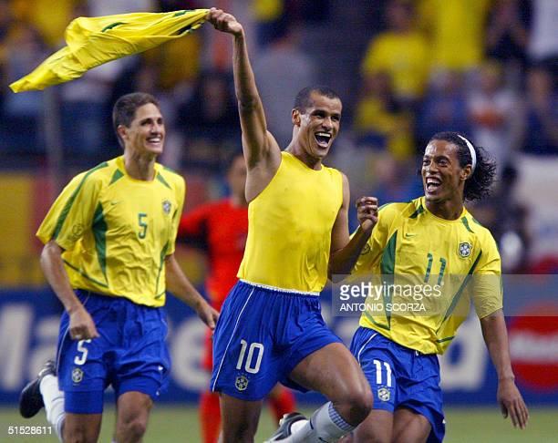 Brazilian midfielder Rivaldo celebrates after scoring as Brazilian midfielder Ronaldinho and Brazilian defender Edmilson look on during the second...