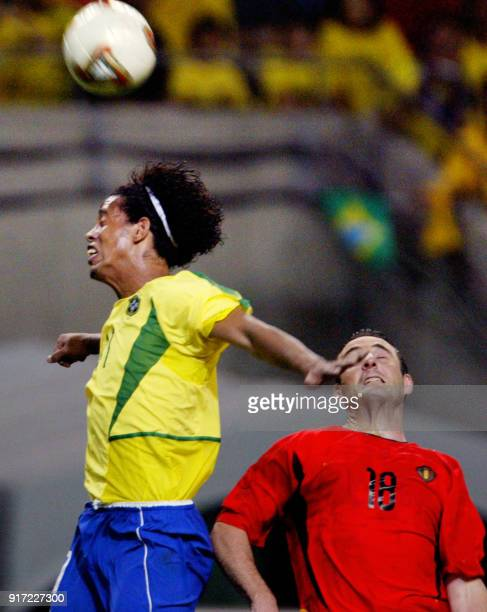 Brazilian midfielder Ronaldinho heads off the ball despite Belgian midfielder Yves Vanderhaeghe during the second round match Brazil/Belgium of the...