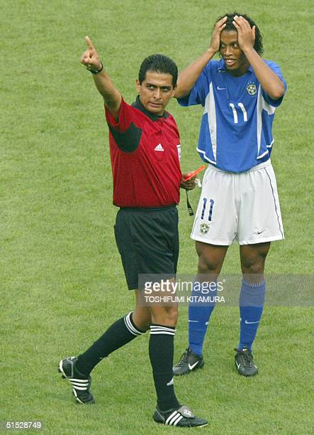Brazilian midfielder Ronaldinho reacts after receiving a yellow card from Mexican referee Felipe Ramos Rizo during the England/Brazil quarterfinal...