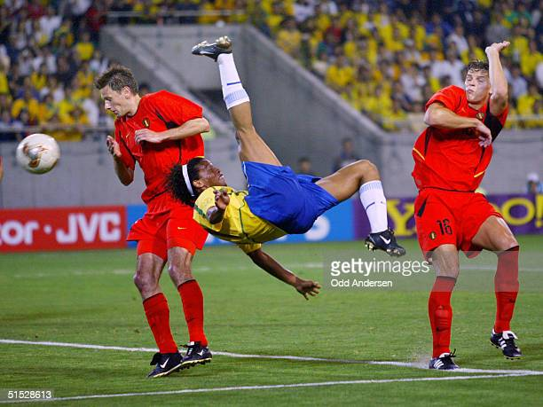 Brazilian midfielder Ronaldinho shoots a high kick as Belgian defender Nico van Kerckhoven and Belgian defender Daniel van Buyten protect their faces...