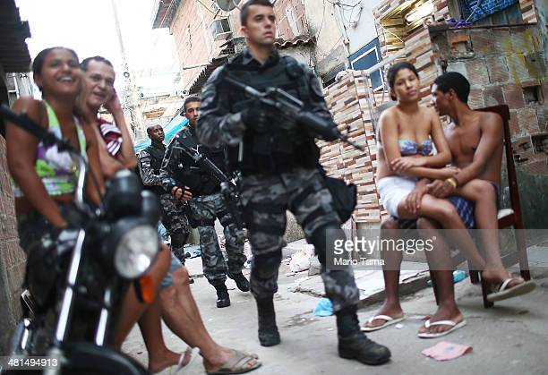Brazilian military police officers patrol after entering the unpacified Complexo da Mare, one of the largest 'favela' complexes in Rio, on March 30,...