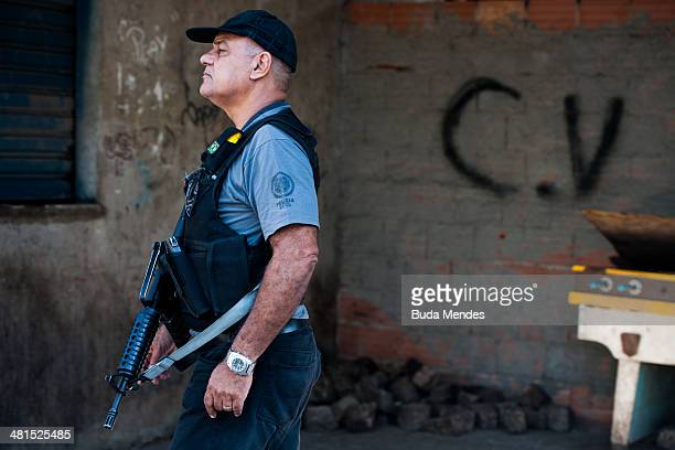 Brazilian military police patrol with the symbol at the bottom of the criminal group Comando Vermelho after entering the unpacified Complexo da Mare...