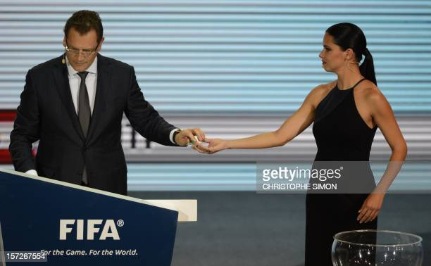 Brazilian model Adriana Lima and FIFA secretary general Jerome Valcke draw a ball during the draw for next June's Confederations Cup Brazil 2013 a...