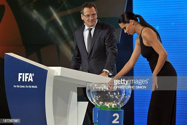Brazilian model Adriana Lima drawa a ball as FIFA secretary general Jerome Valcke looks on during the draw for next June's Confederations Cup Brazil...