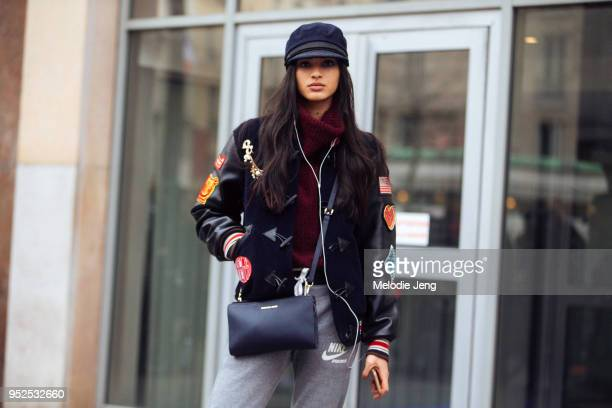 Brazilian model Aira Ferreira uses earphones and wears an engineer hat black toggle varsity jacket with patches a maroon turtleneck a Michael Kors...