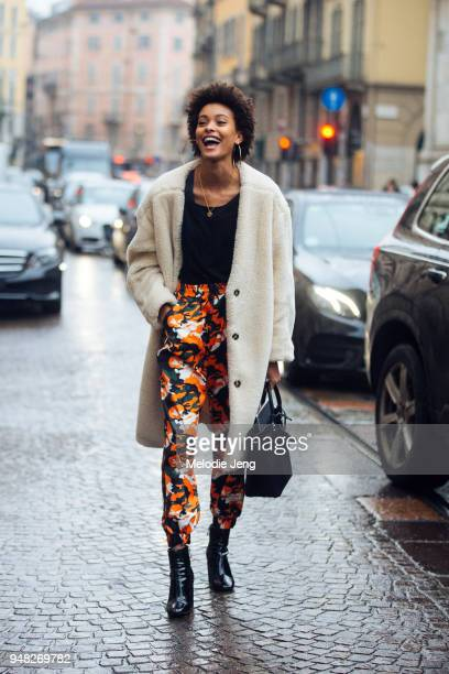Brazilian model Samile Bermannelli wears large hoop earrings a white teddy bear coat a black top orange camo print pants black booties and a black...