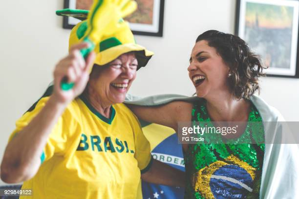 Brazilian mother and daughter watching soccer game at home