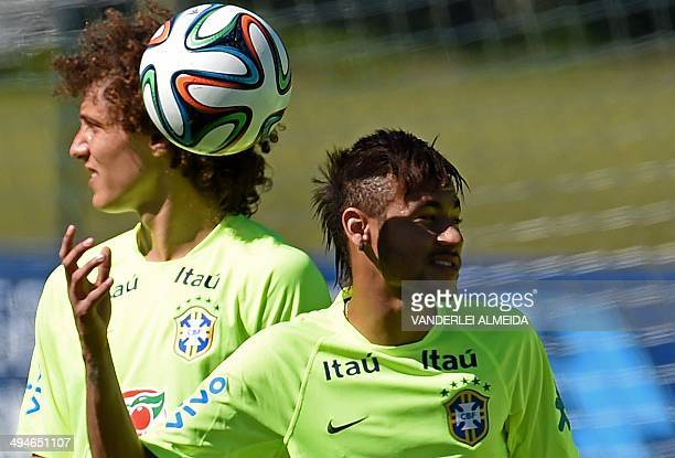 Brazilian national footballer Neymar plays with a ball next to teammate David Luiz during a training session at the Granja Comary training complex in...