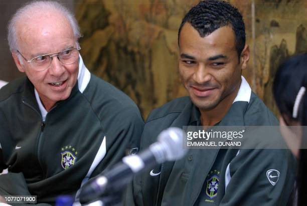 Brazilian national team caretaker coach Mario Zagallo and team captain Cafu smile to a South Korean translator 19 November 2002 during a press...