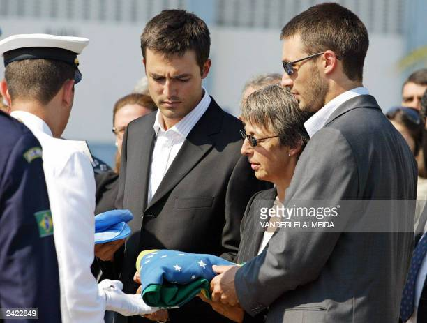 A Brazilian Navy cadet gives to slain UN diplomat Sergio Vieira de Mello's sons Adrian and Bernard and widow Annie the Brazilian and UN flags during...