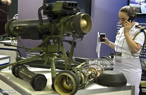 A Brazilian Navy female officer stands by a Serbianmade Bumbar antitank missile system on display at the FAP stand during the second day of the LADD...