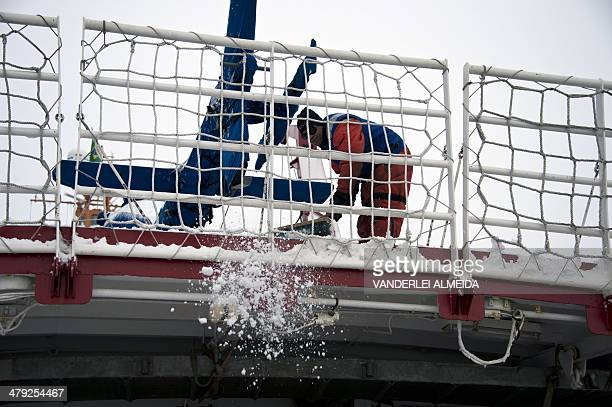 Brazilian Navy marines clear snow from the deck of Brazil's Navy oceanographic ship Ary Rongel during operations in Antarctica on March 12 2014 AFP...