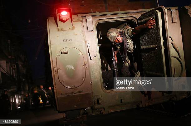 Brazilian Navy soldiers enter the unpacified Complexo da Mare one of the largest 'favela' complexes in Rio on March 30 2014 in Rio de Janeiro Brazil...