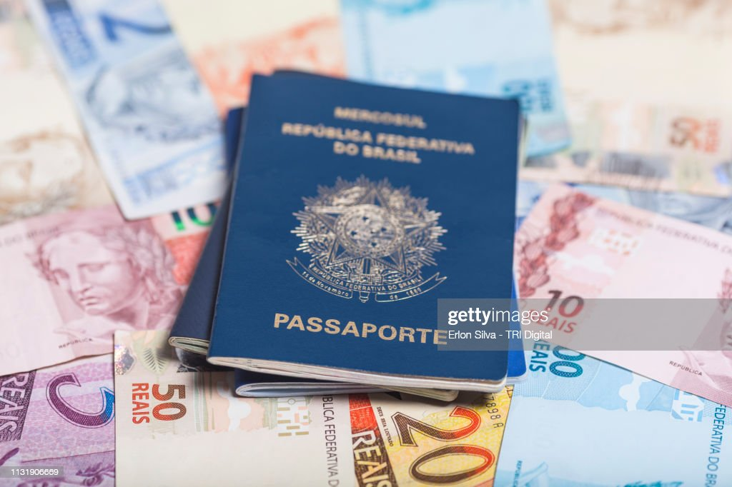 Brazilian passport on top of Brazilian real notes of various values : ストックフォト