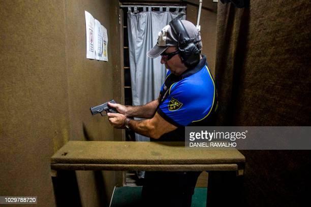 Brazilian Paulo Alberto prepares to shoot at the 'Calibre 12' shooting club in Sao Goncalo Rio de Janeiro Brazil on September 03 2018 The liberation...