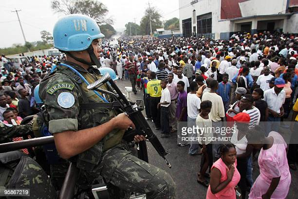 Brazilian peacekeepers under UN command ride a jeep past thousands of Haitians lining up to vote in the lower Delmas neighborhood in Port-Au-Prince,...