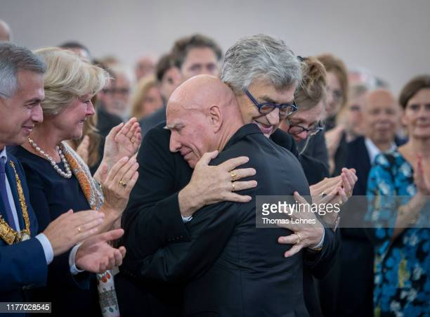 Brazilian photographer Sebastiao Salgado hugs Wim Wenders after his speech during the Peace Prize of the German Book Trade award ceremony at St....