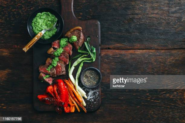 ブラジルのピカニャステーキ、新鮮なハーブソースと野菜のグリル - チミチュリ・ソース ストックフォトと画像