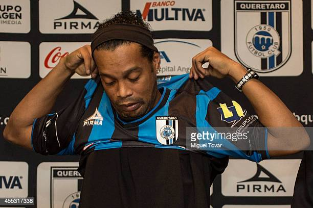 Brazilian player Ronaldinho Gaucho poses for pictures wearing his jersey during a press conference to unveil as a new player at Camino Real Hotel on...