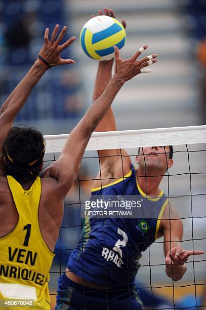 Brazilian player Vitor Araujo hits the the ball at Jackson Henriquez of Venezuela during their men's Beach Volleyball Preliminary match at the 2015...