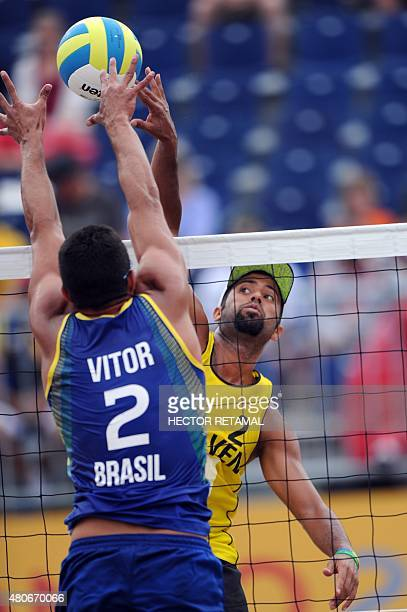 Brazilian player Vitor Araujo tries to block against Jesus Villafane of Venezuela during their men's Beach Volleyball Preliminary match at the 2015...