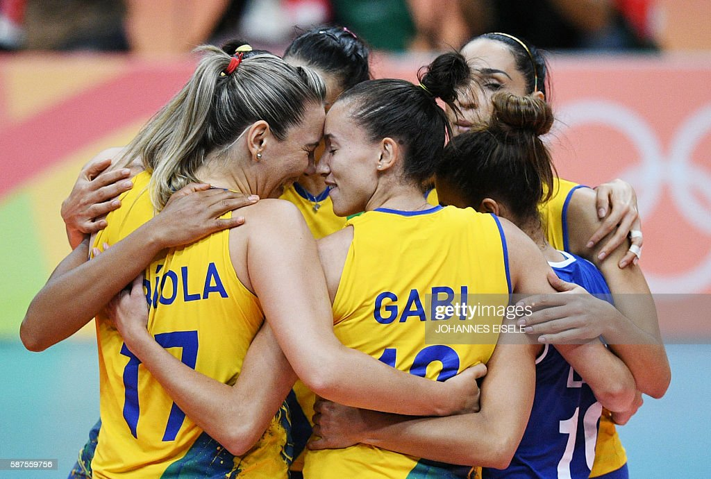 TOPSHOT - Brazilian players celebrate after winning the women's qualifying volleyball match between Brazil and Argentina at the Maracanazinho stadium in Rio de Janeiro on August 8, 2016, during the 2016 Rio Olympics. / AFP / Johannes EISELE