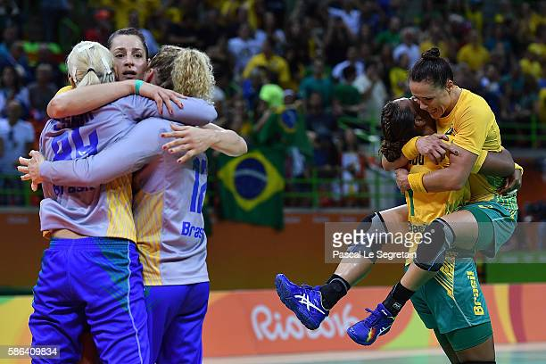Brazilian players celebrate their victory at the end of the women's preliminaries Group A handball match Norway vs Brazil on Day 1 of the Rio 2016...