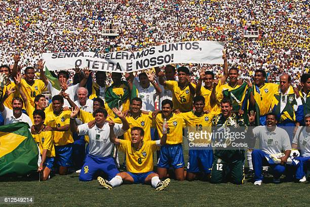 Brazilian players celebrate their victory over Italy in the final of the 1994 FIFA World Cup. They hold a banner in Ayrton Senna's memory.