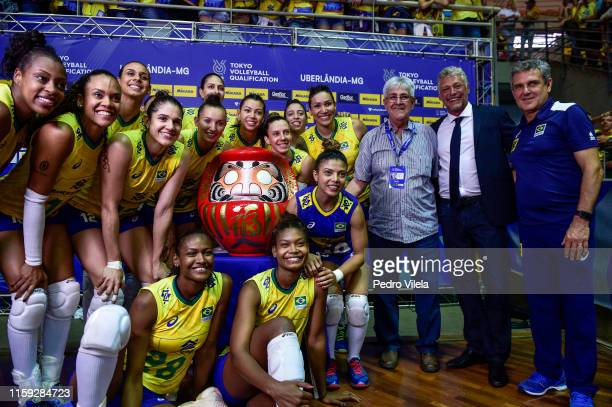 Brazilian players lift the Japanese Daruma doll after the victory on the women's qualifying volleyball match between the Brazil and Dominican...