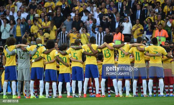 Brazilian players link arms during the playing of national anthems ahead of the semifinal football match between Brazil and Germany at The Mineirao...