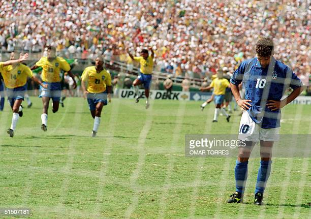 Brazilian players run to join their teammates as Italian midfielder Roberto Baggio bows his head after he missed his penalty kick giving Brazil a 3-2...