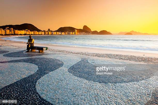 Brazilian poet Carlos Drummond de Andrade statue at Copacabana beach sidewalk Rio de Janeiro Brazil The Copacabana promenade is a pavement landscape...