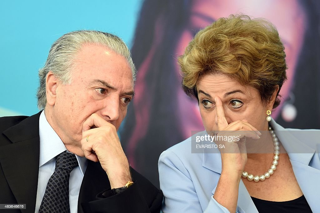 Brazilian President Dilma Rousseff (R) and Vice-President Michel Temer attend the launching ceremony of the Investment Program in Energy at Planalto Palace in Brasilia, on August 11, 2015. Analysts say Brazil's once booming economy suffers deep underlying illnesses, notably the massive corruption scandal unfolding at national oil company Petrobras and rippling across other top companies and into political circles. It is also on the brink of recession. According to a recent poll that put Rousseff's approval rating at eight percent, she is now Brazil's most unpopular democratically elected president since a military dictatorship ended in 1985.