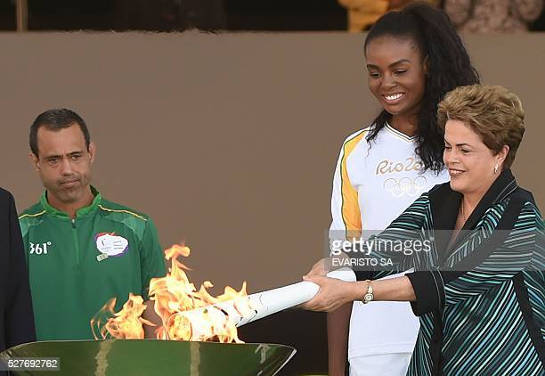 Brazilian President Dilma Rousseff hands the Olympic torch to Brazilian volleyball player Fabiana Claudino at Planalto Palace in Brasilia following...